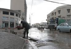 أحد طواقم بلدية غزة يقوم بتصريف مياه الأمطار