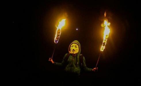 شباب من غزة يحمل شعلة نار خلال الارباك الليلي على حدود القطاع
