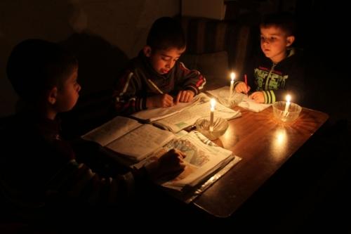 أطفال يدرسون على الشموع
